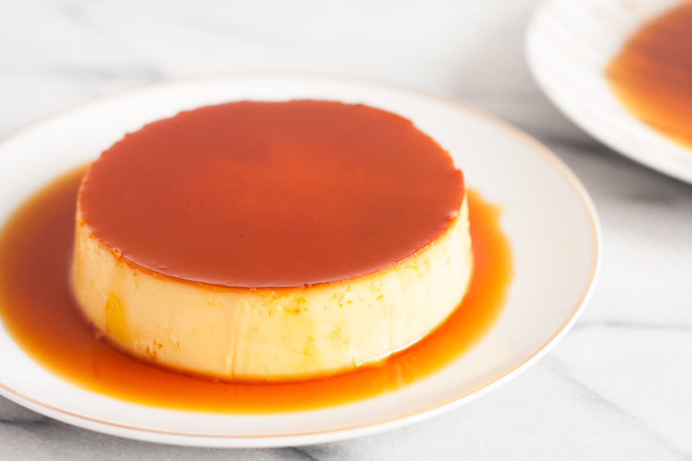 The Ultimate Creme Caramel (Leche Flan) Recipe - a perfect balance of a sweet egg custard with a slight punch of lemon. It's definitely rich, smooth, and creamy! | www.SpoonfulOfButter.com