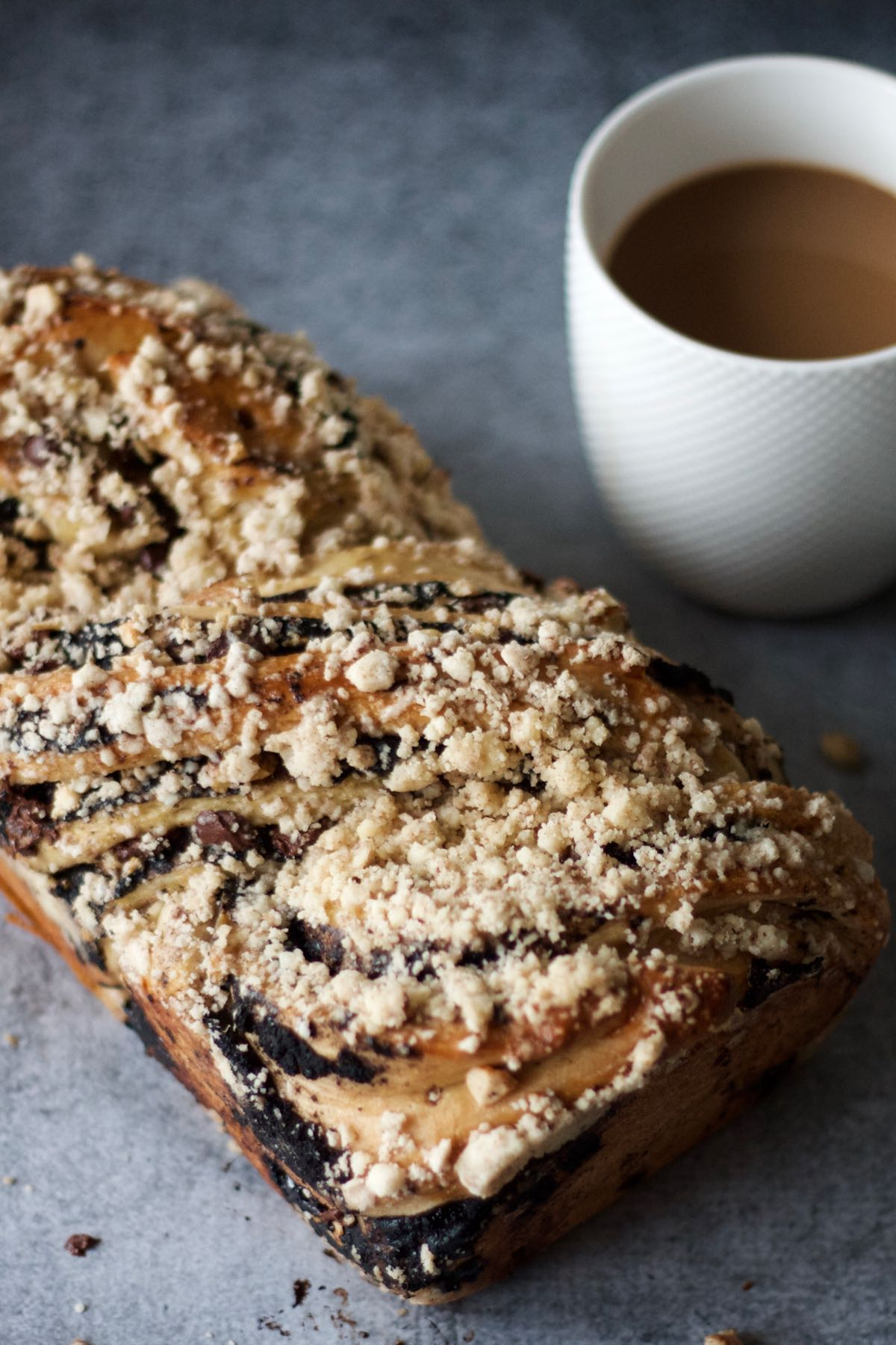 A whole loaf of Dark Chocolate and Cashew Babka with coffee on the side