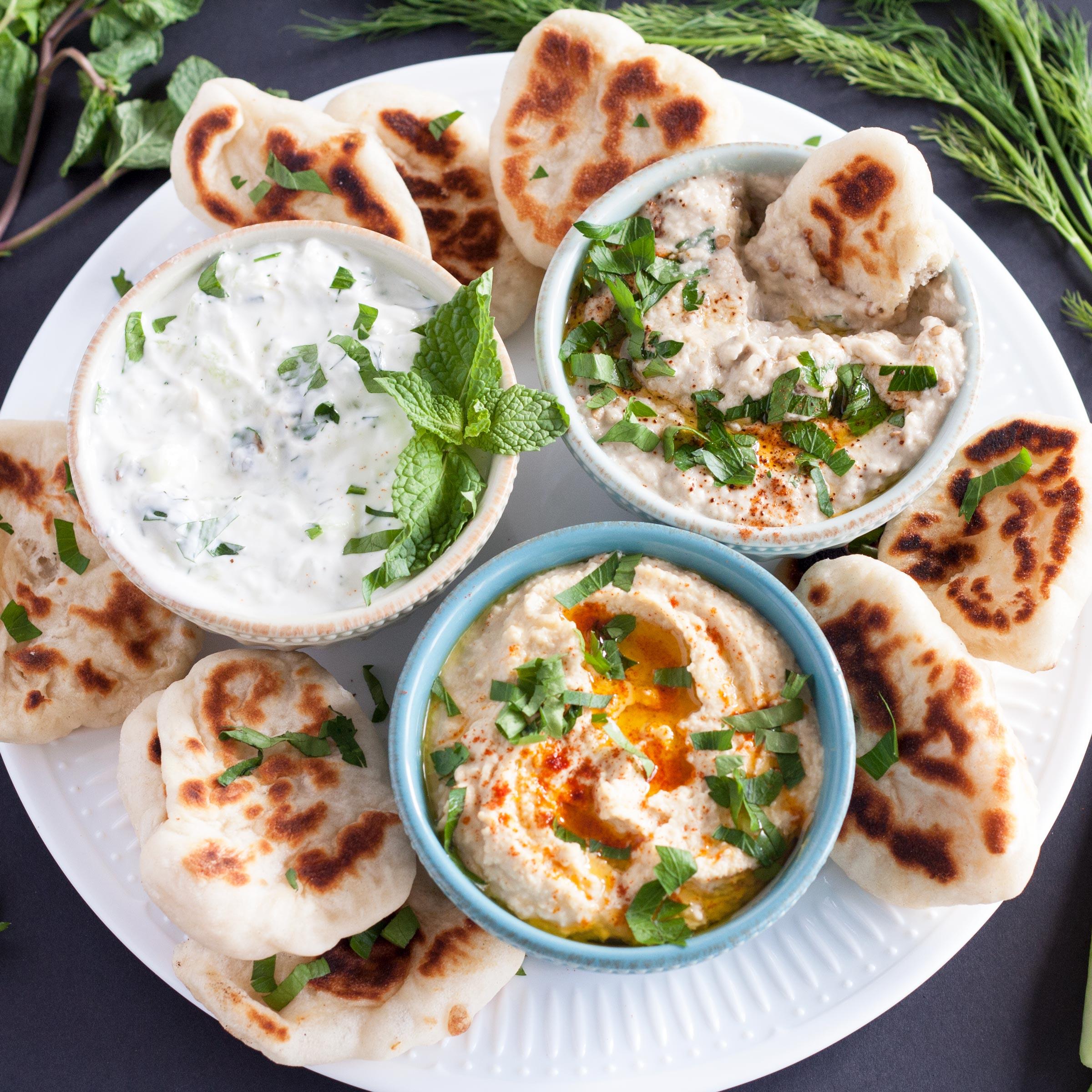 A Mezze Platter consists of Hummus, Baba Ganoush, Tzatziki, and Naan Dippers