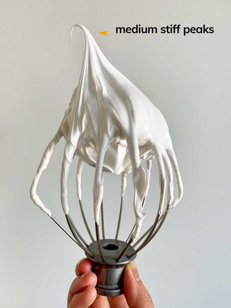 A whisk attachment with whipped egg whites at medium-high speed