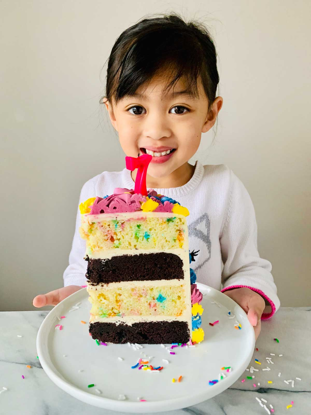 mica holding a slice of the unicorn birthday cake