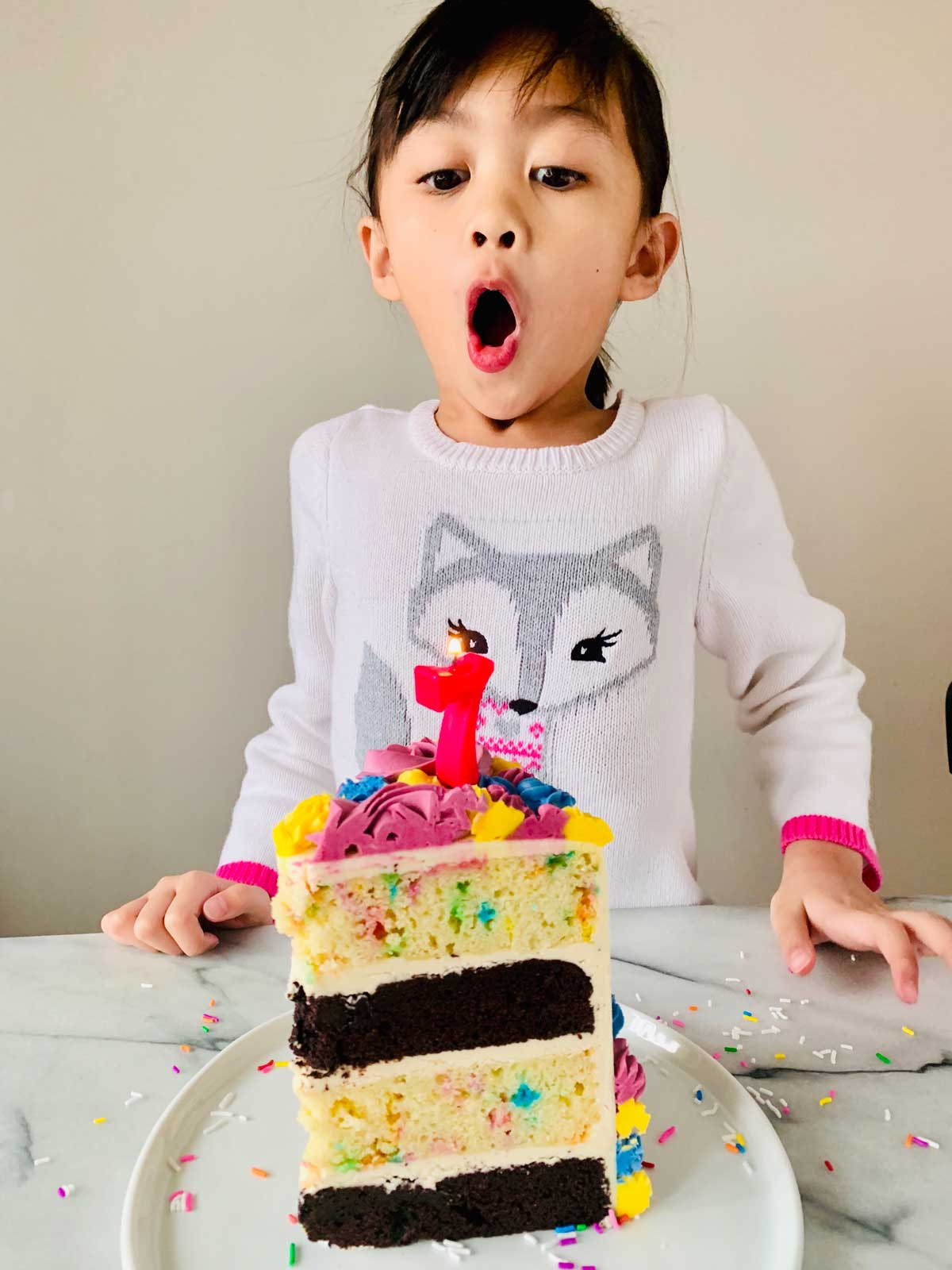 mica blowing her unicorn birthday cake