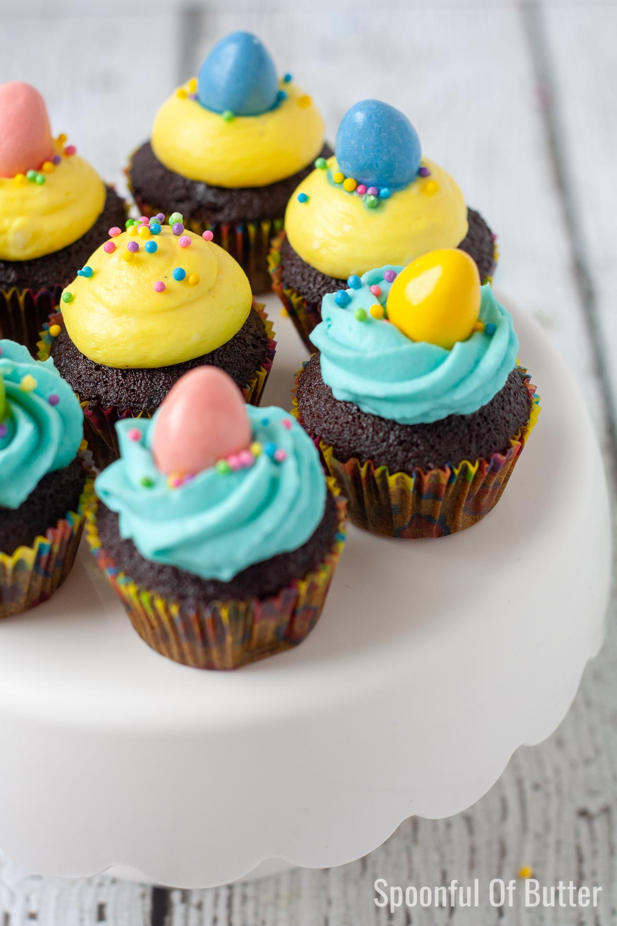 mini easter chocolate cupcakes with cream cheese frosting on a cake stand