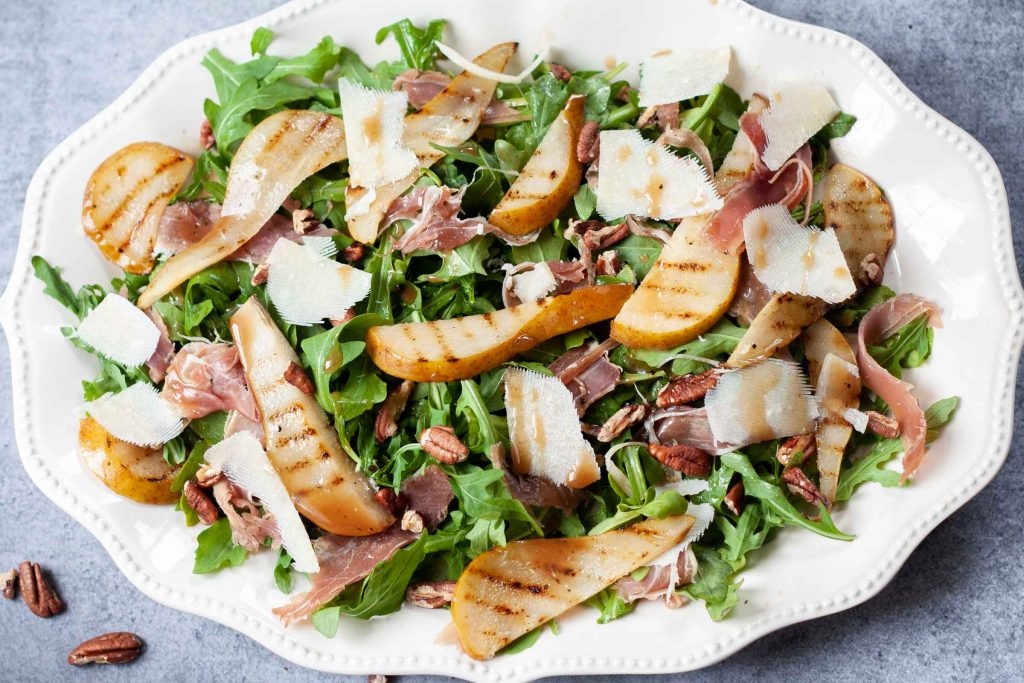 pear, prosciutto, and arugula salad on a serving plate